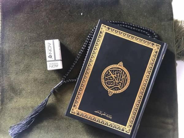 Tapis vert kaki et Coran noir